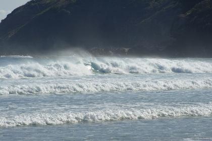 崖下の強い白波に飲まれるサーファー