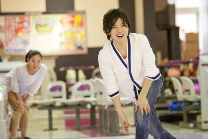 ボウリングをする男性と見つめる女性