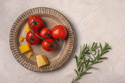 Cherry tomatoes, parmesan cheese on a ceramic plate and rosemary twig