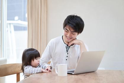 テレワークをしながら子守をするアジア人のお父さん
