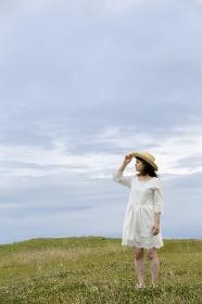 草原で麦わら帽子をかぶって立つ日本人女性