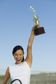 Female tennis player on tennis court holding up trophy portrait