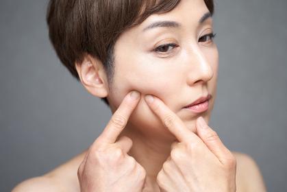 肌荒れを気にする中年の日本人女性