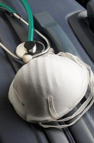 Mask and stethoscope on suitcase