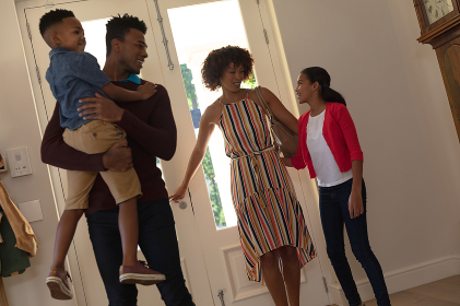 Happy african american couple with son and daughter embracing and smiling at home. family enjoying quality free time together.