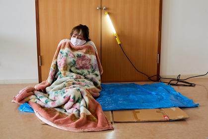 避難所イメージ 災害にあって避難所の体育館に避難してきたシニア女性