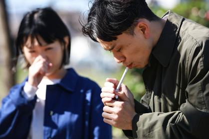 タバコを吸う男性と嫌がる女性