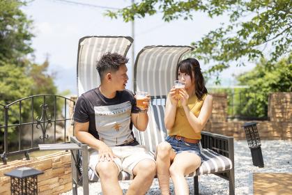 別荘の庭でビールを飲むカップル