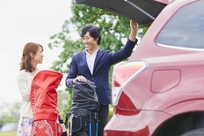 トランクからゴルフバッグを降ろす日本人カップル