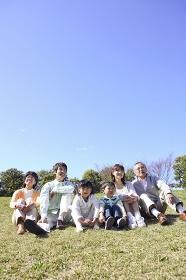 芝生に座る三世代ファミリー