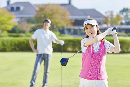 ゴルフをする日本人カップル