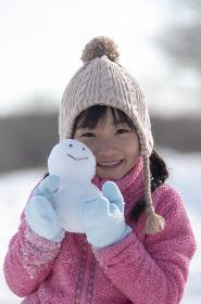 雪原で雪だるまを持つ女の子