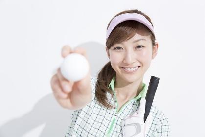 ゴルフボールを持つ笑顔の女性