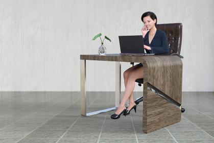 おしゃれでシンプルなオフィスで革製の椅子に座りノートパソコンを見るビジネスウーマン