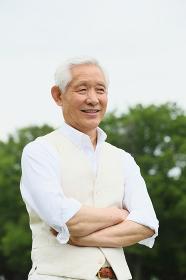 緑と腕を組むシニアの日本人男性