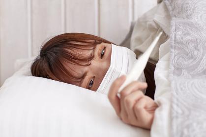 体温計で熱を測る日本人女性