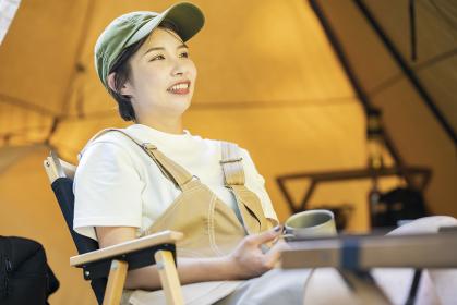 キャンプサイトでリラックスする若い女性
