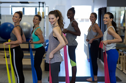 Smiling women performing stretching exercise with resistance band