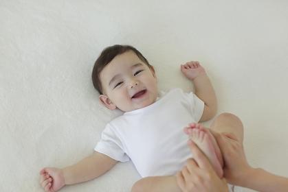 ベッドの上に寝転がる赤ちゃんとママの手