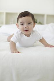 ベッドの上で腹ばいする赤ちゃん