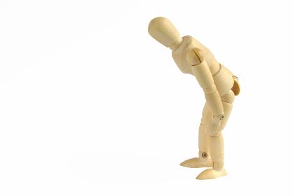 腰が痛いポーズをした横向きの木製のモデル人形