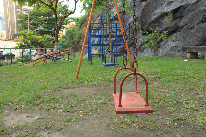 A kids playground on a park right next to a rock wall