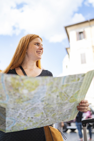 pretty red hair woman with a city map is smiling looking around
