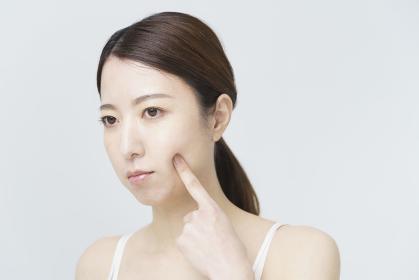 頬を触って肌の状態をチェックする女性