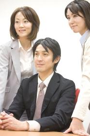 椅子に座るビジネスマンの両脇に立つOL2人