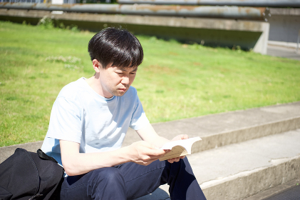 ステップに腰掛け読書をする男性