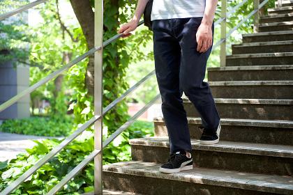爽やかな新緑の階段を降る男性