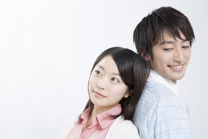 背中を合わせて微笑むカップル