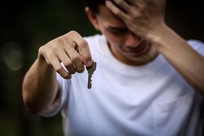 泣きながら鍵を渡す男性