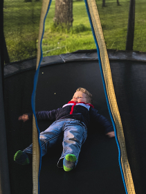 the boy lies on the trampoline