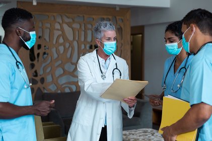 Caucasian female senior doctor and diverse hospital colleagues wearing face masks talking at meeting. medicine, health and healthcare services during covid 19 coronavirus pandemic. .