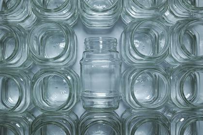 一面に並べたインスタントコーヒーの空き瓶。中央の一つだけが倒れている。リサイクルの空き瓶。真俯瞰撮影