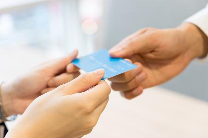 クレジットカードを店員に手渡す女性・パーツカット(決済・支払い・キャッシュレス)