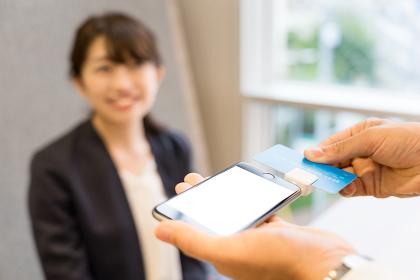 スマートフォンでクレジットカードの決済をする女性