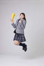 メガホンを持ちジャンプする女子中学生