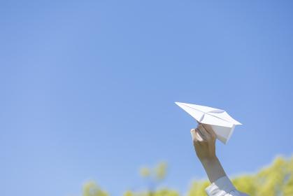 手作りの紙飛行機を持つ若い女性女性