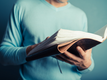 A young man wearing a blue jumper is flipping through a big notebook