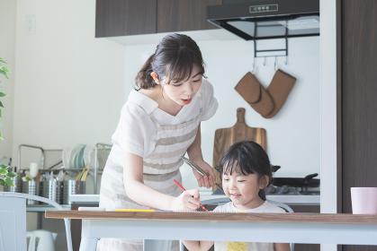 キッチンでお絵かきをする女の子と、料理をしながら見守る母親