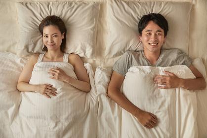 布団に入る笑顔の日本人夫婦