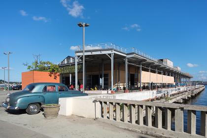 キューバ・ハバナの水辺の商業施設とヴィンテージカー