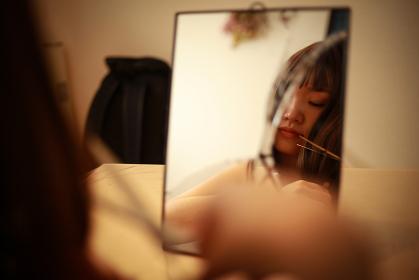 割れた鏡の前で髪を切る女性