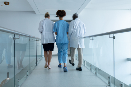 Three diverse male and female doctors walking through hospital corridor talking. medicine, health and healthcare services.