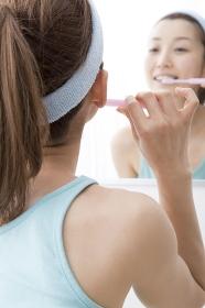鏡の前で歯を磨く女性