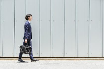 歩く若いビジネスマン(通勤・外回り)・コピースペースのある画像