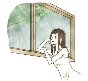 雨の日に窓の外を眺める女性