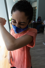 Mixed race woman wearing face mask sneezing into her elbow. hygiene in workplace during coronavirus covid 19 pandemic